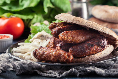 Cevapcici or cevapi served with lepinja bread and onion. Popular dish all over the Balkans 版權商用圖片