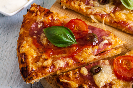 Slices of pizza with bacon, olives and tomatoes on cutting board. Stock Photo