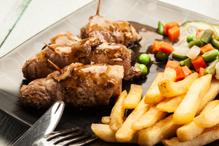 Pork rolls with french fries with vegetable on a plate