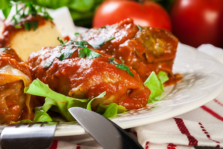 Stuffed cabbage with meat and rice served with boiled potatoes and tomato sauce on white plate