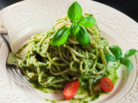 Pasta spaghetti with homemade basil pesto sauce on white plate