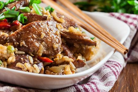 Arroz frito con pollo y verduras servido en un plato. Plato chino popular Foto de archivo