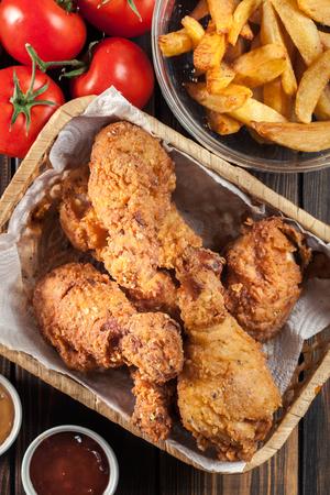 Breaded crispy fried kentucky chicken drumctick in the basket. Top view