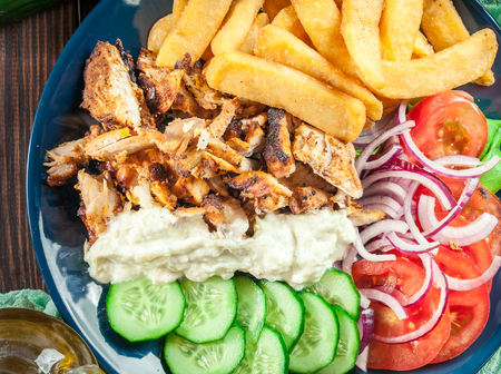 Greek gyros dish with french fries and vegetables. Served with tzatziki sauce Stock Photo