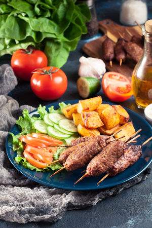 Grilled shish kebab served with fried potatoes and vegetable salad Фото со стока