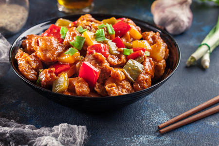 Sweet and sour chicken with colorful bell pepper on a plate. Chinese dish Standard-Bild