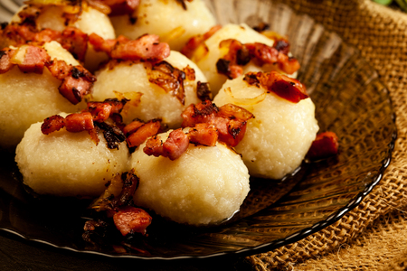 Potato dumplings stuffed with meat served with bacon on a plate Фото со стока