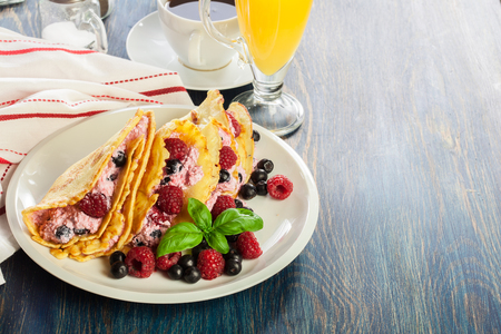 Delicious tasty homemade traditional crepes with cottage cheese, raspberries, and chokeberry