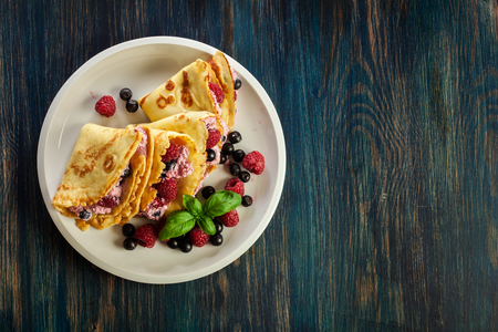 Delicious tasty homemade traditional crepes with cottage cheese, raspberries, and chokeberry. Top view