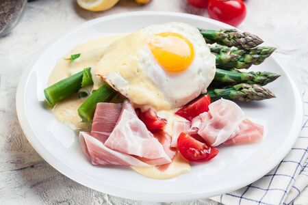 Green asparagus with prosciutto ham, fried egg and hollandaise sauce. Spring dish