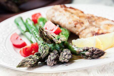 Filetto di merluzzo fritto con asparagi verdi. piatto di primavera Archivio Fotografico