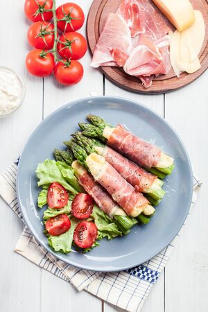 Baked prosciutto and cheese wrapped asparagus served with salad