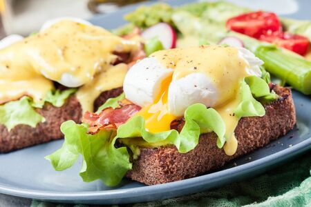 Sandwiches with bacon and poached egg. Served with hollandaise sauce and asparagus