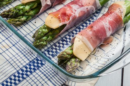 Prosciutto and cheese wrapped asparagus ready for baked