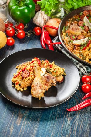 Traditional paella with chicken legs, sausage chorizo and vegetables served on black plate. Spanish cuisine. Top view Stockfoto