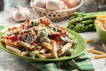 Penne pasta with green asparagus, parma ham and mushrooms in a cheese sauce. Topped with parmesan cheese