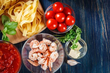 Ingredients ready for preparing pappardelle pasta with shrimp, tomatoes and herbs. Italian cuisine. Top view Stock Photo