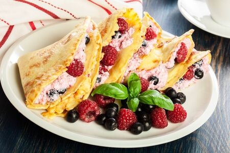 Delicious tasty homemade traditional crepes with cottage cheese, raspberries, and chokeberry Archivio Fotografico