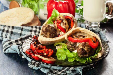 Tasty kofta kebab with grilled paprika and onion served on pita flatbread