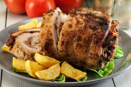 Roasted pork roll stuffed with other meat and dried tomatoes served with fried potatoes