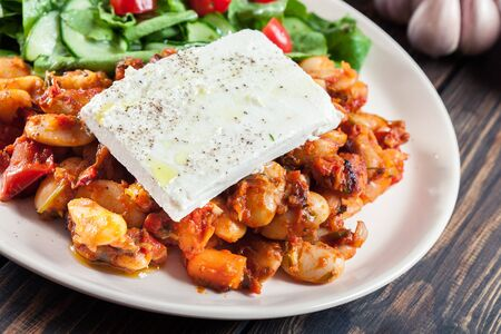 Baked giant beans with feta cheese and tomato sauce. Greek traditional food Zdjęcie Seryjne