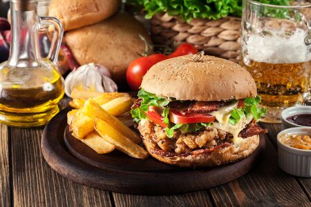 Chickenburger with bacon, tomato, cheese and lettuce served with french fries and beer