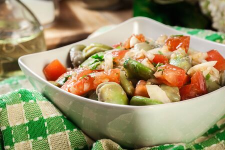 Broad bean salad with tomatoes, onion and olive in white bowl 写真素材