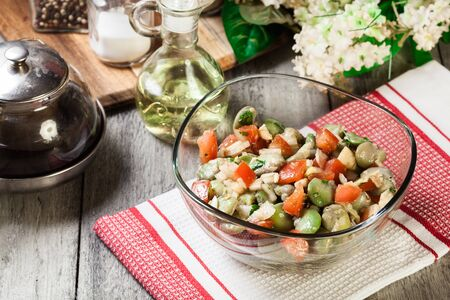Broad bean salad with tomatoes, onion and olive in glass dish 写真素材