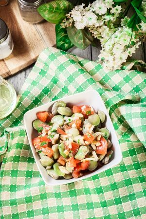 Broad bean salad with tomatoes, onion and olive in white bowl. Top view