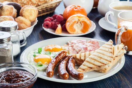 Fresh english breakfast with sausage, eggs and toast