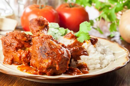 Chicken drumstick curry with rice served on a plate Stock Photo - 129592989