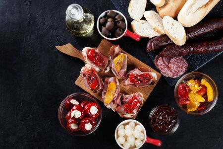 Spanish tapas with slices jamon serrano and grilled pepper. Also olives, salami, pickled onions, and peppers stuffed with cheese. Spanish cuisine. Top view.