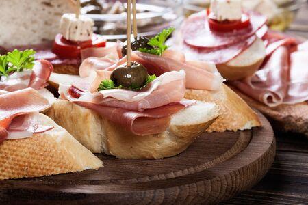 Tapas spagnole con fette di jamon serrano, salame, olive e cubetti di formaggio su un tavolo di legno. Cucina spagnola