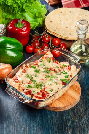 Traditional mexican enchiladas with chicken meat, spicy tomato sauce and cheese in heat resistant dish. Mexican cuisine.
