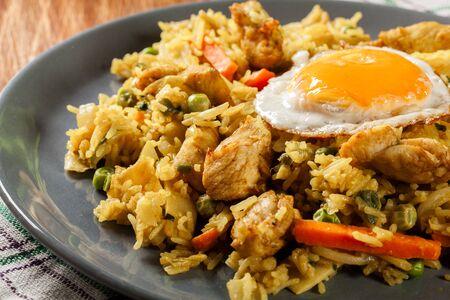 Gebratener Reis Nasi Goreng mit Hühnerei und Gemüse auf einem Teller. Indonesische Küche.
