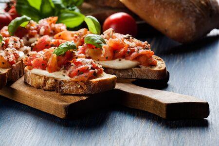 Bruschetta italiana con pomodori arrostiti, mozzarella ed erbe aromatiche su un tagliere