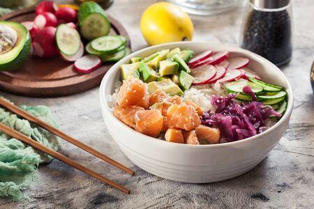 Poke bowl, traditional Hawaiian raw fish salad with rice, avocado, cucumber and radish on bright background