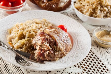 Pork knuckle with fried sauerkraut and tomatoes on white plate