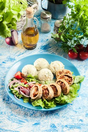Pork rolls stuffed with mozzarella and sun-dried tomatoes served with mashed potatoes and salad