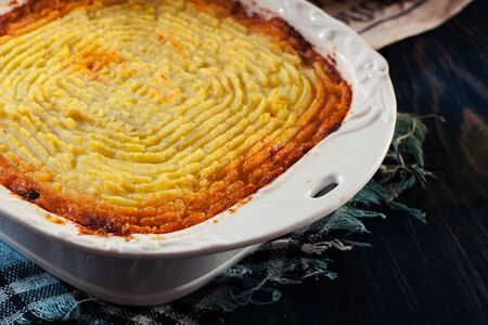 Shepherd's pie or cottage pie. Minced beef meat and vegetables with mashed potatoes in casserole dish
