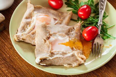 Galette complete. Crepes with ham, cheese and poached egg on a plate. French cuisine