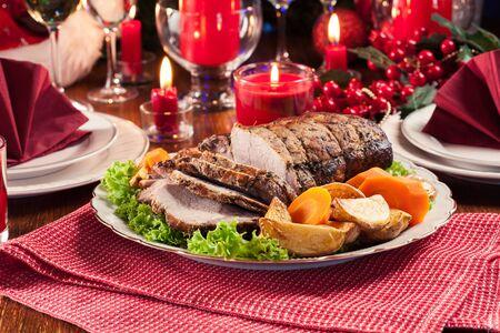 Lonza di maiale arrosto con patate e verdure al forno. Atmosfera natalizia Archivio Fotografico