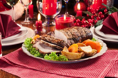Roasted pork loin with baked potatoes and vegetables. Christmas atmosphere Foto de archivo
