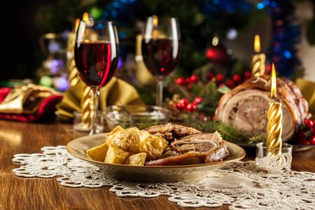 Traditional italian porchetta. Rolled pork belly with baked potatoes on festive table Stockfoto