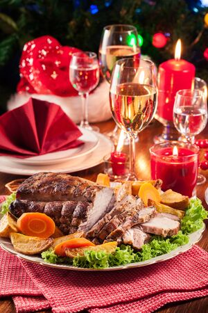 Roasted pork loin with baked potatoes and vegetables. Christmas atmosphere Stock Photo
