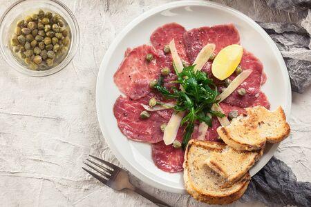Beef carpaccio with arugula and parmesan. Italian dish Stock Photo