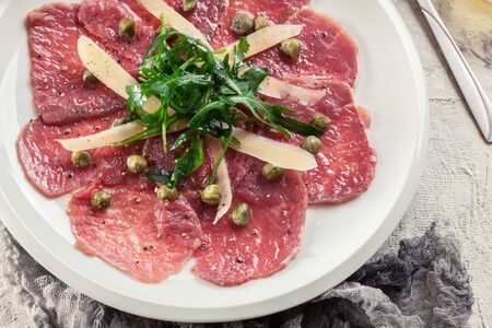 Beef carpaccio with arugula and parmesan. Italian dish 免版税图像