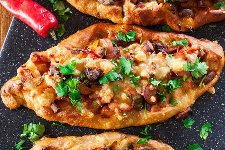 Traditional Turkish pide with meat and vegetables on cutting board. Top view 版權商用圖片