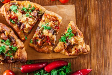 Sliced traditional Turkish pide with meat and vegetables on cutting board. Top view 版權商用圖片