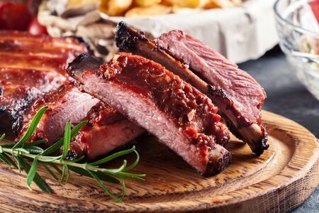 Spicy barbecued pork ribs served with BBQ sauce on chopping board
